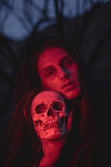 Mens die in rood lichten een schedel houdt door zijn hoofd