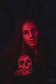 Mens die in rood lichtschaduwen in dark met schedel zit