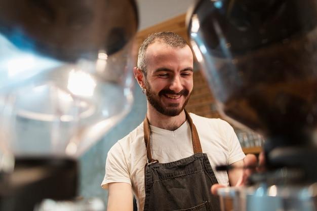 Mens die in schort glimlacht en koffie maakt