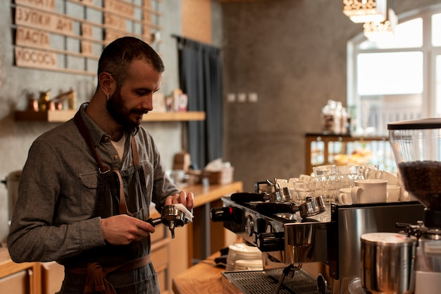 Mens die in schort koffie voorbereiden bij machine