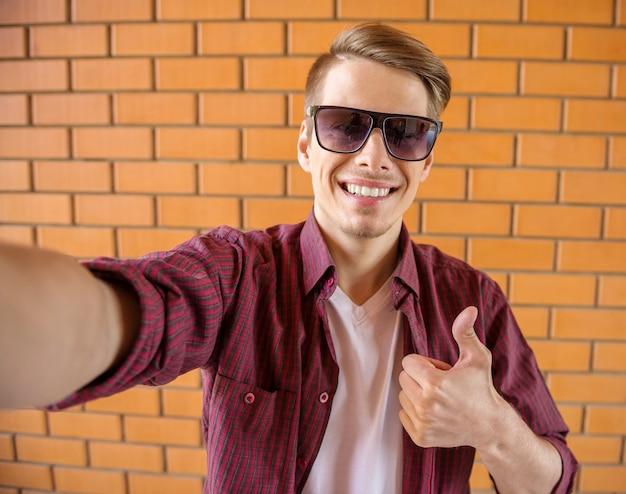 Mens die in slimme vrijetijdskleding selfie op bakstenen muur maakt.