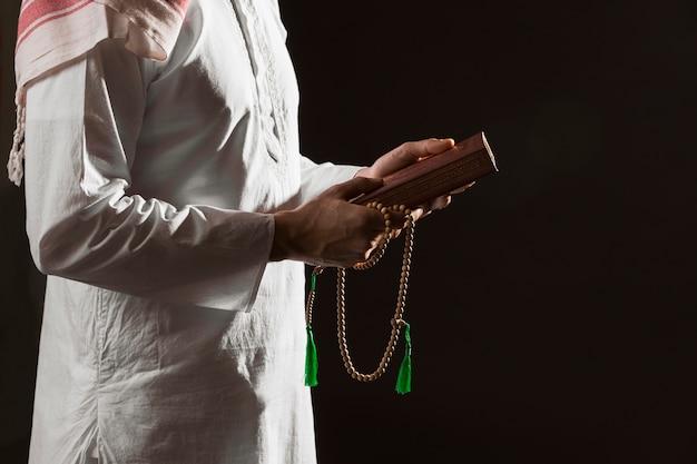 Mens die in traditionele arabische kleren koran houdt