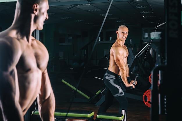 Mens die in trainer voor tricepsspieren uitoefenen in de gymnastiek