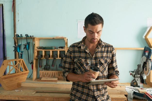 Mens die in vrijetijdskleding e-mails met houtbewerking op de achtergrond controleert