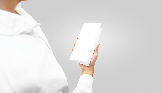 Mens die in wit overhemd leeg brochureboekje in de hand houdt.
