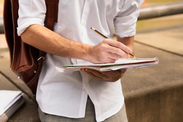 Mens die in wit overhemd met potlood op papier schrijft