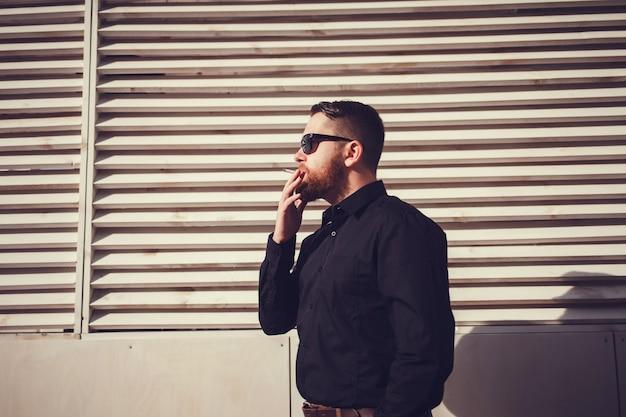 Mens die in zonnebril een sigaret rookt