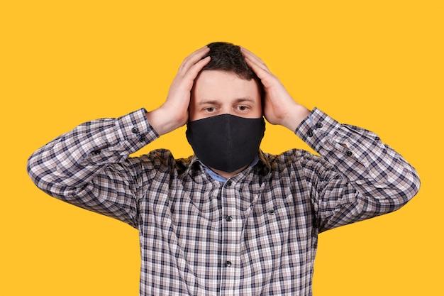 Mens die in zwart gezichtsmasker zijn hoofd met handen houdt, die op oranje ruimte wordt geïsoleerd.
