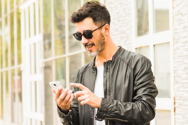 Mens die in zwart jasje zonnebril draagt die mobiele telefoon met behulp van