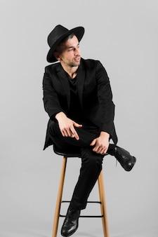 Mens die in zwart kostuum weg en op een stoel zit kijkt