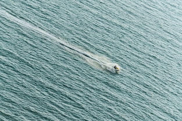 Mens die jetski op het overzees met bespattend waterspoor op de overzeese oppervlakte bevrijden.