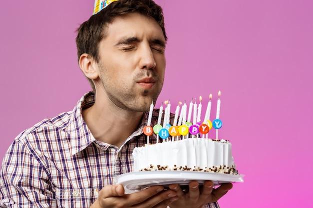 Mens die kaarsen op verjaardagscake uitblazen over purpere muur.