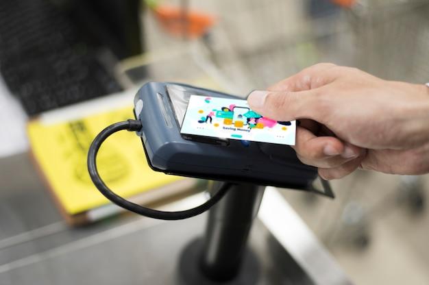 Mens die kaart gebruikt om in winkel te betalen
