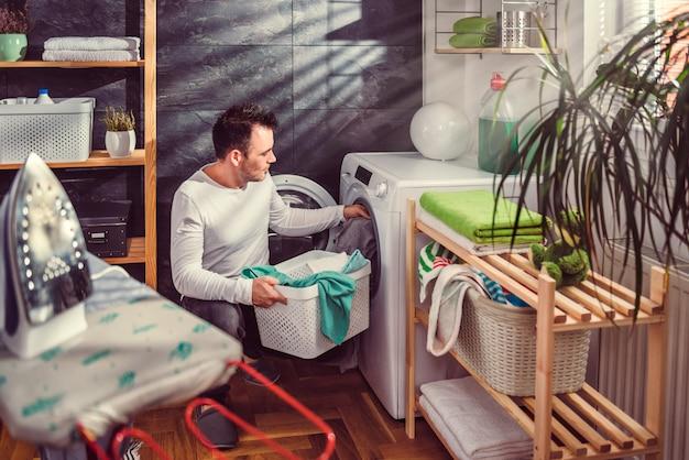 Mens die kleren zet in wasmachine