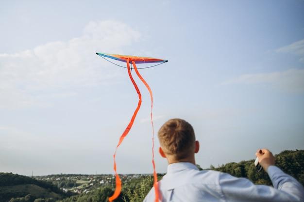 Mens die kleurrijke luchtvlieger op het gebied lanceert