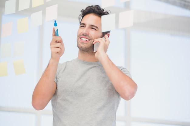 Mens die kleverige nota's bekijkt terwijl het spreken op telefoon