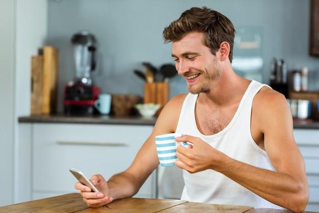 Mens die koffie heeft terwijl thuis het gebruiken van mobiele telefoon