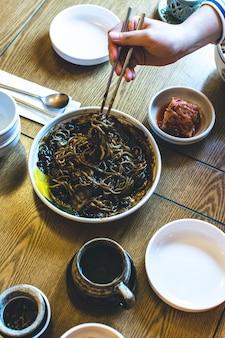 Mens die koreaanse noedels in dikke zoete sojasaus eet met eetstokjes
