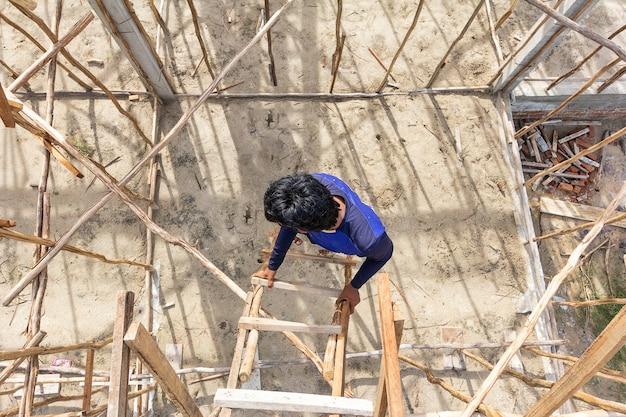 Mens die laars draagt die tijdelijke houten trede in bouwwerf gebruikt om op en neer te gaan.