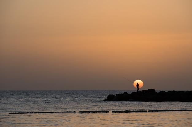 Mens die, lage zon vissen bij het amadores-strand op het eiland van gran canaria in spanje.
