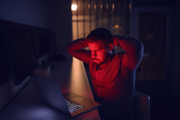 Mens die laptop bekijkt en laat in de nacht in het bureau zit.