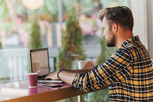 Mens die laptop in koffiewinkel met behulp van