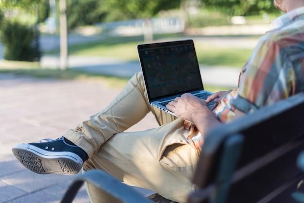 Mens die laptop in park met behulp van