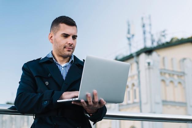 Mens die laptop in stedelijke omgeving met behulp van