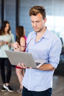 Mens die laptop met behulp van terwijl collega's die zich erachter in bureau bevinden