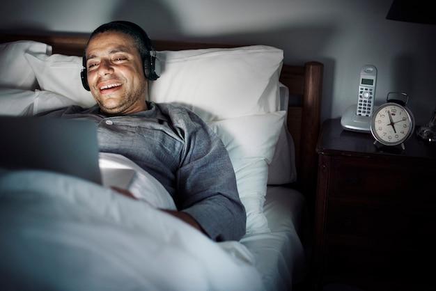 Mens die laptop op een bed met behulp van