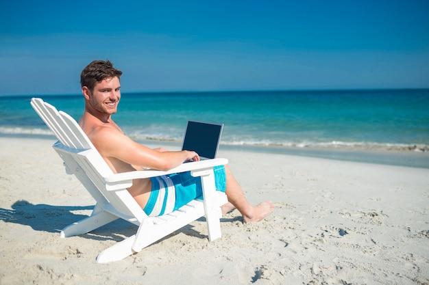 Mens die laptop op ligstoel met behulp van bij het strand