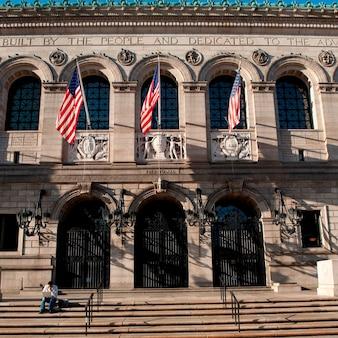 Mens die laptop voor een gebouw in boston, massachusetts, de vs met behulp van