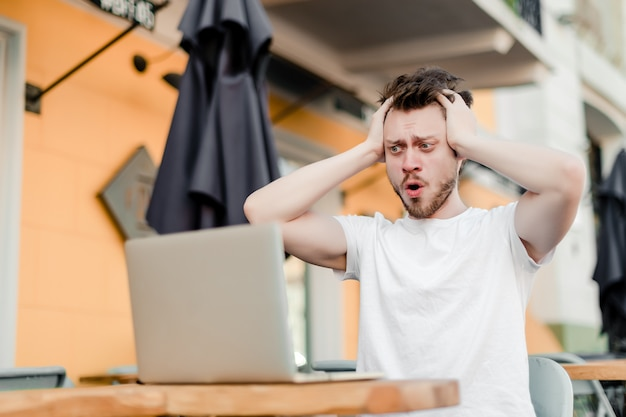 Mens die laptop voor het verre werk in koffie met behulp van