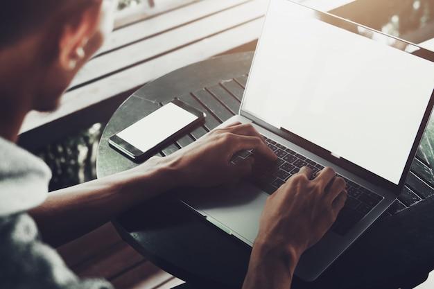 Mens die laptop voor het werken met behulp van online bij koffiewinkel