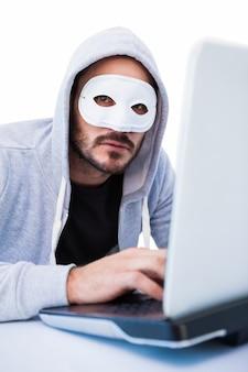 Mens die masker draagt terwijl het binnendringen in laptop