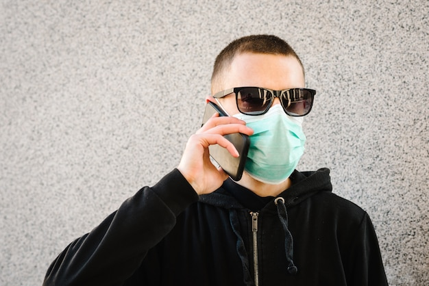 Mens die medisch beschermend masker draagt en op cel mobiele telefoon spreekt, op grijze muur