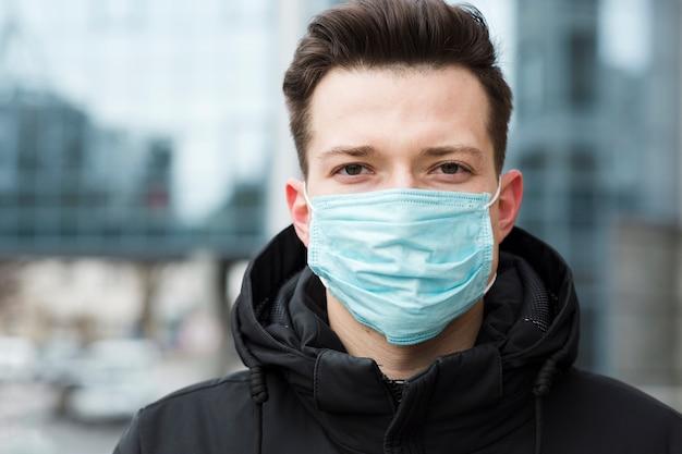 Mens die medisch masker in de stad draagt