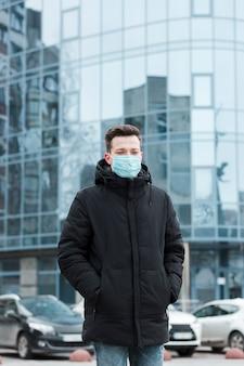 Mens die medisch masker in de stad met exemplaarruimte draagt