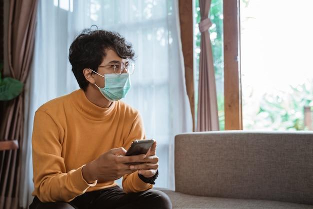 Mens die medische maskers draagt die mobiele telefoon met behulp van tijdens virusepidemische lockdown