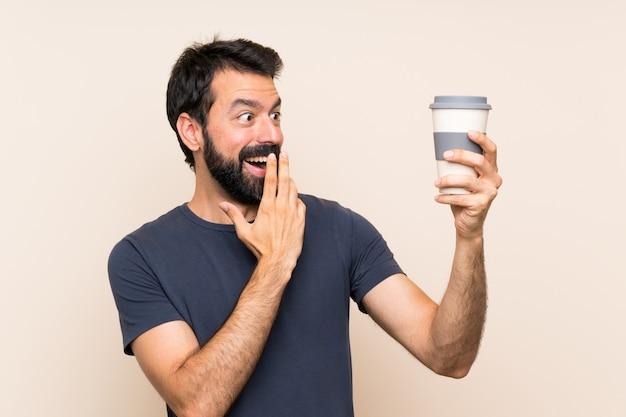 Mens die met baard een koffie met verrassing en geschokte gelaatsuitdrukking houdt