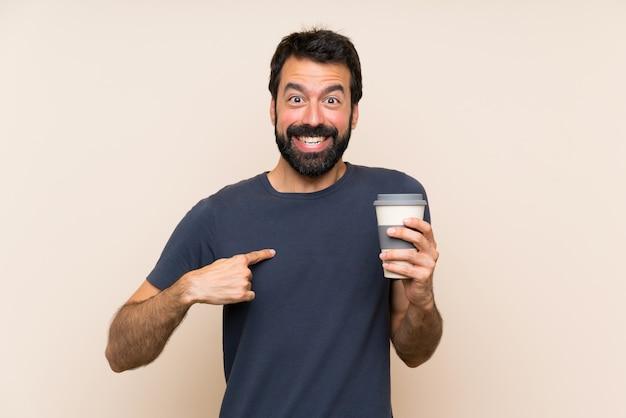 Mens die met baard een koffie met verrassingsgelaatsuitdrukking houdt