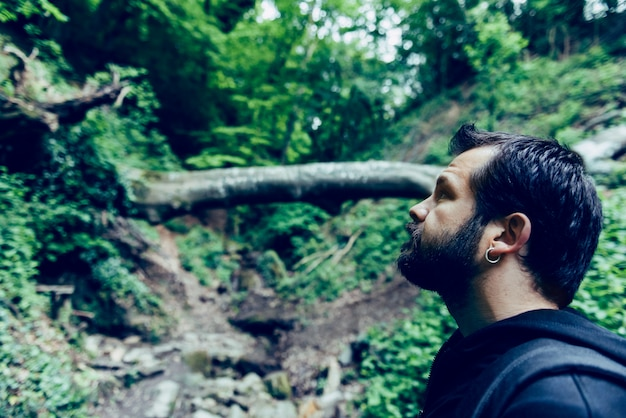 Mens die met baard omhoog in het bos kijkt