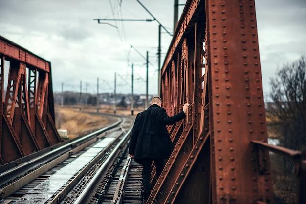 Mens die met baard op de spoorweg loopt
