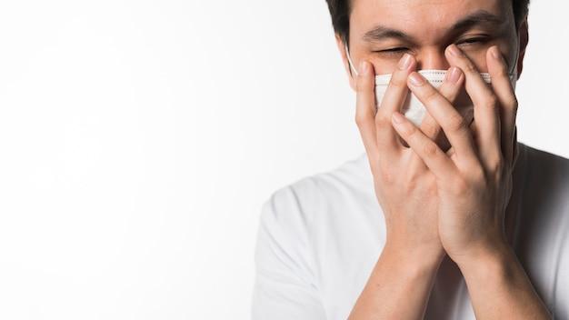 Mens die met coronavirus medisch masker dicht bij mond houdt