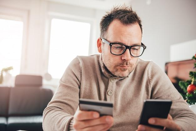 Mens die met creditcard op slimme telefoon betaalt