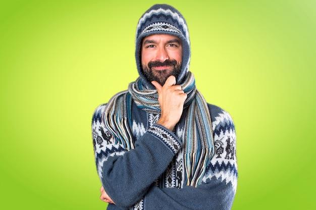 Mens die met de winterkleren op kleurrijke achtergrond denkt