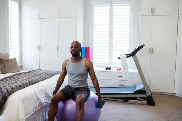 Mens die met domoren op geschiktheidsbal uitoefenen in slaapkamer