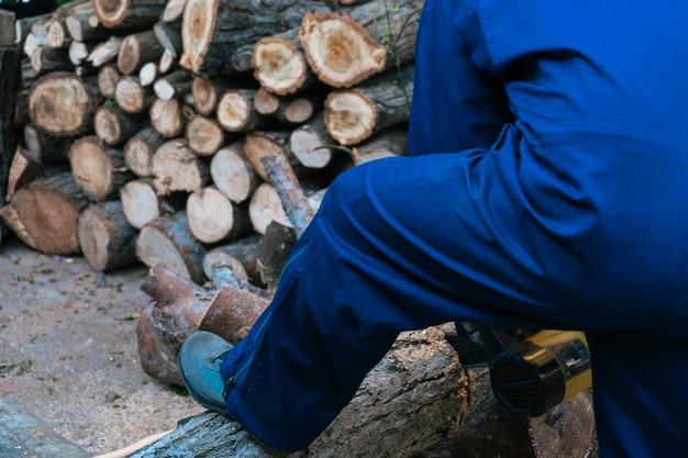 Mens die met een kettingzaag werken die een groot logboek zagen, brandhout oogsten.
