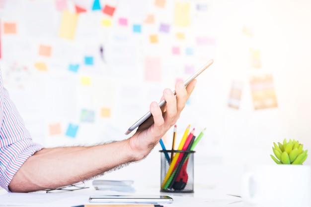 Mens die met een tablet in een bureau werkt