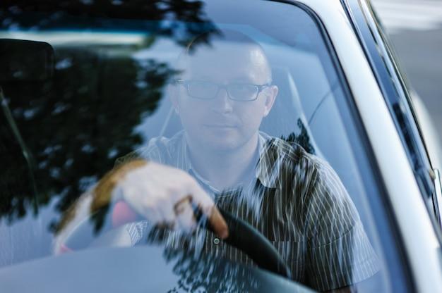 Mens die met glazen achter het stuur van een auto zit